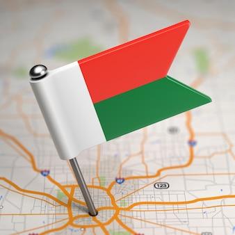 Kleine flagge republik madagaskar auf einem kartenhintergrund mit selektivem fokus.