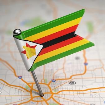 Kleine flagge republik simbabwe auf einem kartenhintergrund mit selektivem fokus.