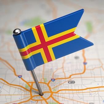 Kleine flagge von aland islands auf einem kartenhintergrund mit selektivem fokus.
