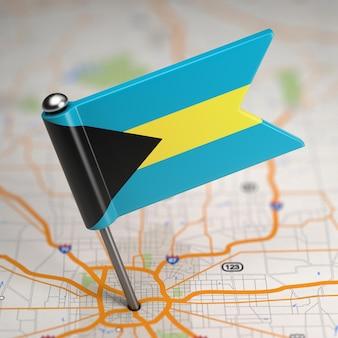 Kleine flagge von bahamas auf einem kartenhintergrund mit selektivem fokus.
