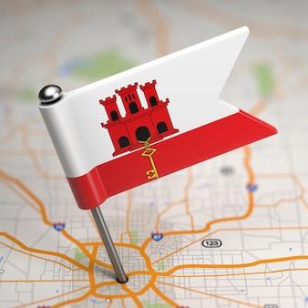 Kleine flagge von gibraltar auf einem kartenhintergrund mit selektivem fokus.