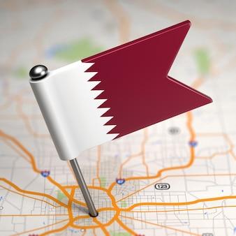Kleine flagge von katar auf einem kartenhintergrund mit selektivem fokus.
