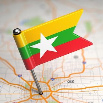 Kleine flagge von myanmar auf einem kartenhintergrund mit selektivem fokus.