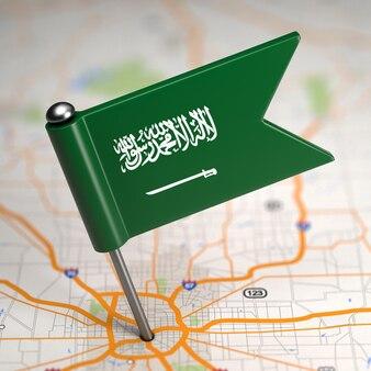 Kleine flagge von saudi-arabien auf einem kartenhintergrund mit selektivem fokus.