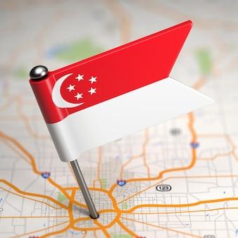 Kleine flagge von singapur auf einem kartenhintergrund mit selektivem fokus.
