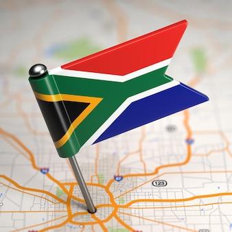 Kleine flagge von südafrika auf einem kartenhintergrund mit selektivem fokus.