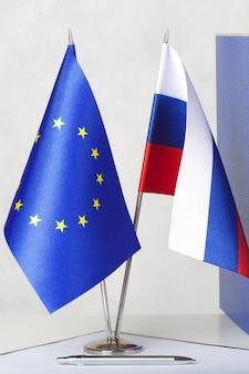Kleine flaggen der europäischen union und der russischen föderation auf einem weißen tisch einige ordner mit dokumenten im hintergrund freier platz für einen text
