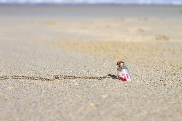 Kleine flasche im weißen hintergrund des sandigen strandes das türkismeer