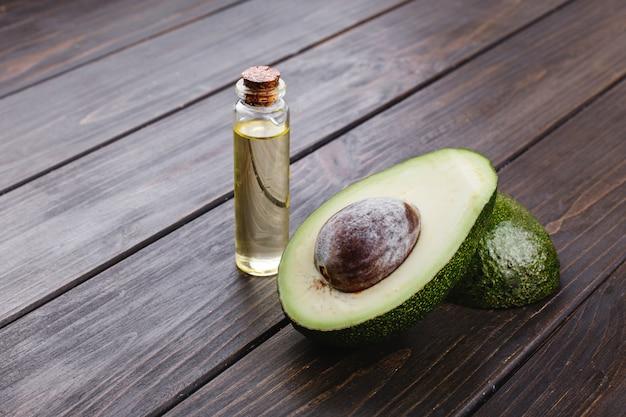 Kleine flasche mit öl und avocado stehen auf dem holztisch