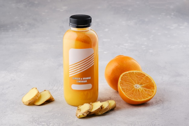Kleine flasche mit orangen-ingwer-limonade auf dem tisch