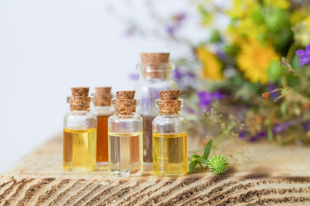 Kleine flaschen mit ätherischen ölen auf holztisch. alternativmedizinisches konzept