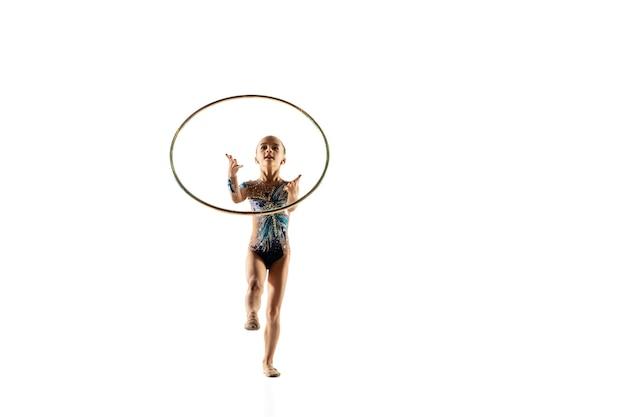 Kleine flexible turnerin isoliert auf weißer wand