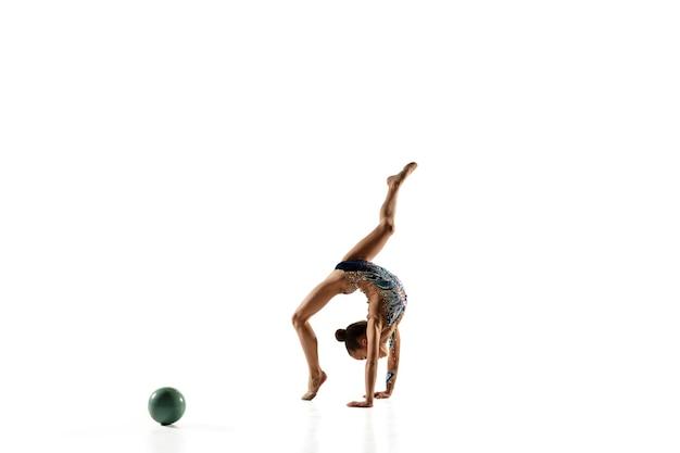 Kleine flexible turnerin lokalisiert auf weißer wand