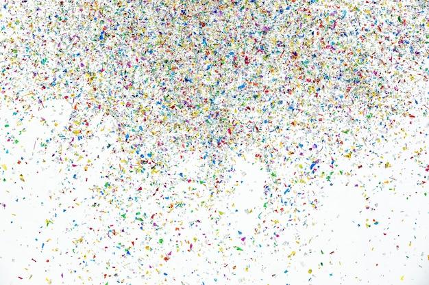 Kleine fragmente von bunten papierstücken werden als schöne feierflocken und lebendige fackeln in die luft gewirbelt, um die party zu unterhalten und zu dekorieren. bilden fröhliches festliches und funkelndes überraschungsereignis