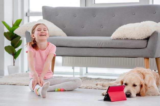 Kleine frau, die auf dem boden mit goldenem retrieverhund sitzt und während des online-yoga lächelt