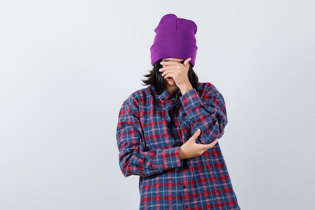 Kleine frau, die hand auf gesicht in kariertem hemd und mütze hält, sieht wehmütig aus