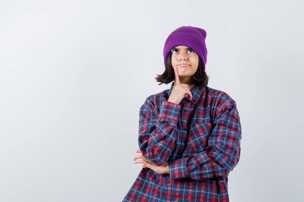 Kleine frau, die in denkender pose mütze steht und nachdenklich aussieht