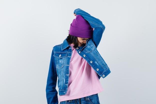 Kleine frau, die in t-shirt-jeans-jacken-mütze den kopf auf den arm lehnt und beleidigt aussieht