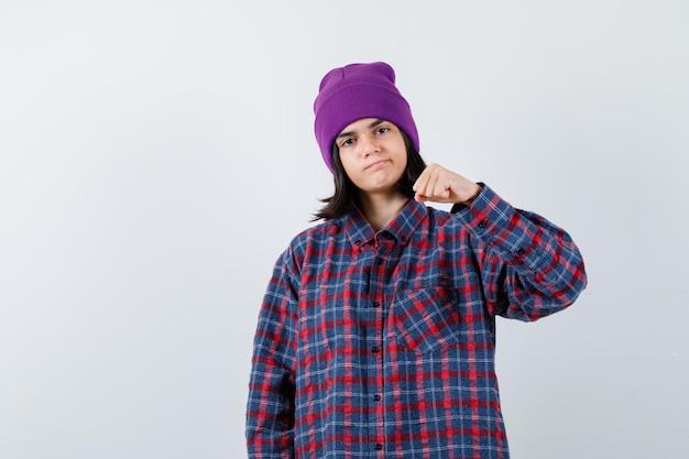 Kleine frau in kariertem hemd und mütze, die geballte faust hebt und selbstbewusst aussieht