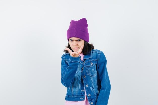 Kleine frau in t-shirt jeansjacke beanie, die die hand in fragender geste ausdehnt