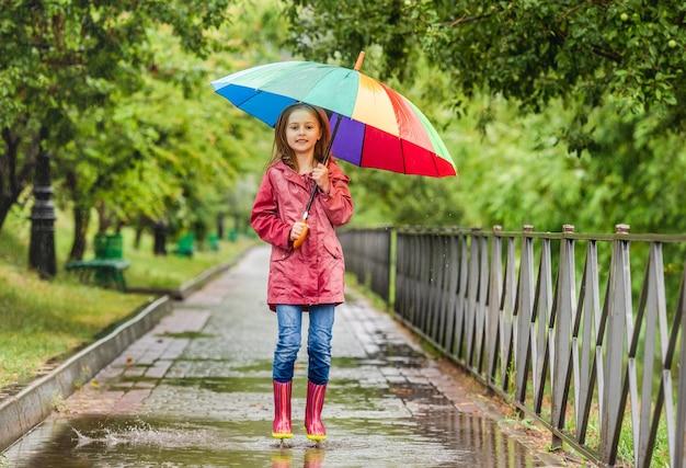 Kleine frau mit regenschirm, der in der pfütze während des regnerischen spaziergangs im park springt