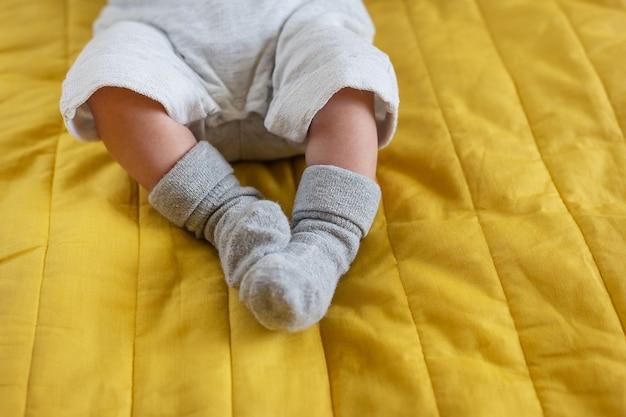 Kleine füße eines neugeborenen in socken. der erste monat im leben eines babys.