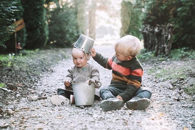 Kleine gartenhelfer kinder spielen mit eimern im garten oder wald