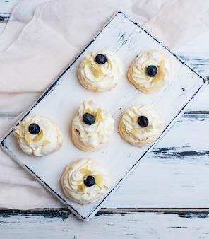 Kleine gebackene runde kuchenbaiser mit schlagsahne