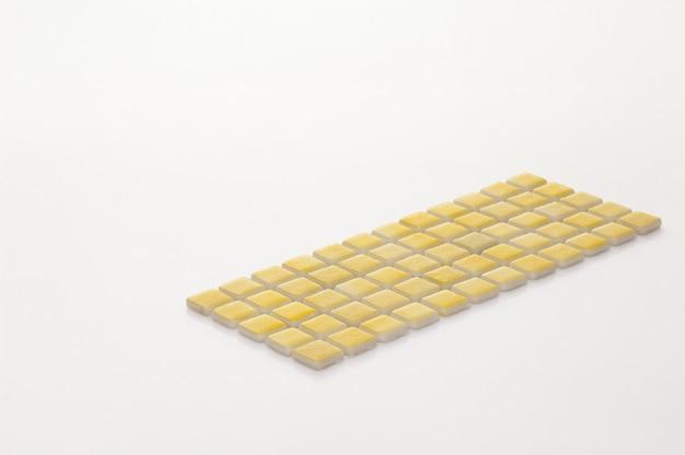 Kleine gelbe keramikfliese auf weißem hintergrund, majolika. für den katalog