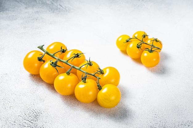 Kleine gelbe kirschtomate auf einem küchentisch. weißer tisch. draufsicht.