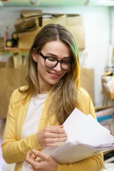 Kleine geschäfts- oder einzelhandelsgeschäftsinhaberin überprüft dokumente für die lieferung von kundenbestellungen im lager