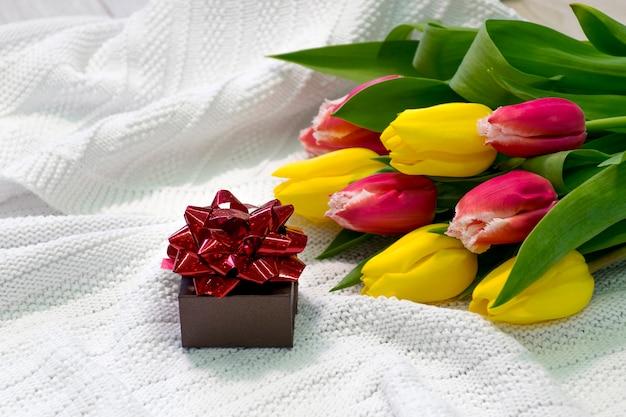 Kleine geschenkbox für schmuck mit roter schleife und strauß bunter tulpen auf weißem stoff