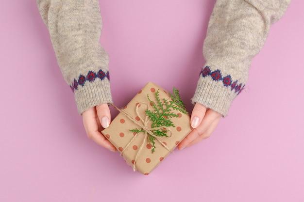 Kleine geschenkbox in den weiblichen händen, ansicht von oben