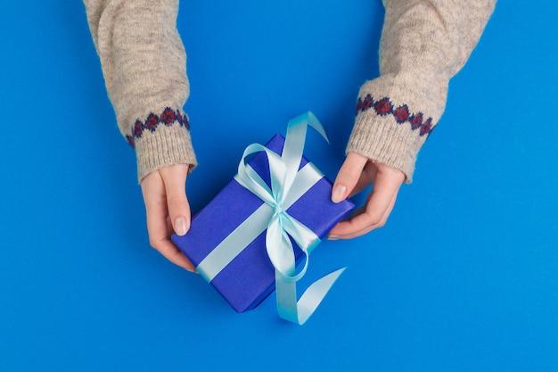 Kleine geschenkbox in den weiblichen händen auf blauem hintergrund, ansicht von oben