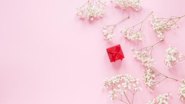 Kleine geschenkbox mit blumenniederlassungen auf tabelle