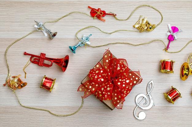 Kleine geschenkbox mit bunter bandfliege auf holztisch mit kleinen dekorativen musikinstrumenten an heiligabend-geburtstagsnacht oder neujahrsfest.
