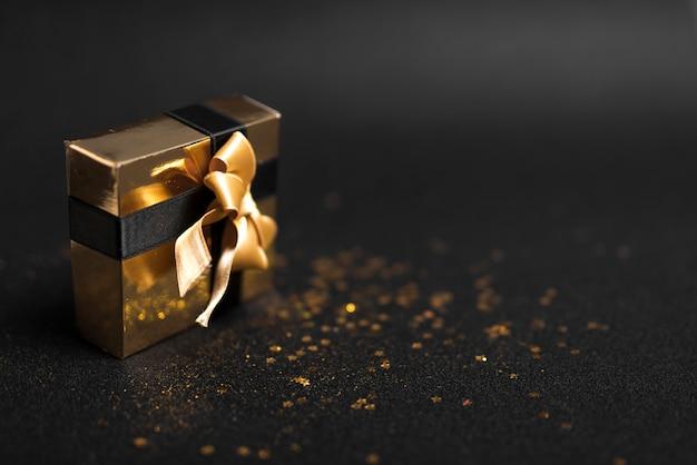 Kleine geschenkbox mit hellen pailletten auf dem tisch