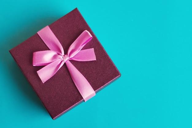 Kleine geschenkbox mit rosa band in türkisfarbener farbe