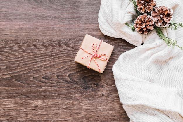 Kleine geschenkbox mit zapfen auf dem tisch