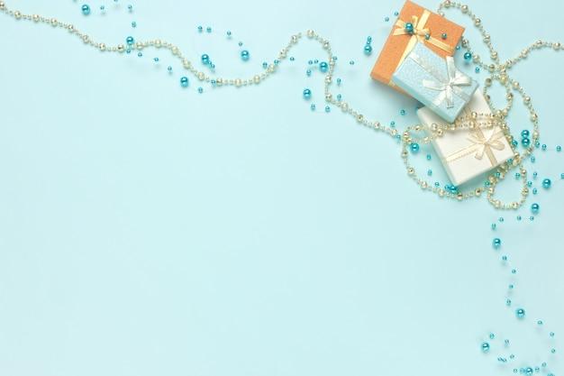 Kleine geschenkboxen auf pastelltürkishintergrundebenenlage. weihnachtsgeschenke, glänzende perlendekorationen. kopieren sie platz.