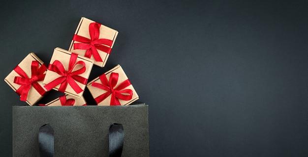 Kleine geschenkboxen in schwarzer einkaufstasche auf schwarzem hintergrund