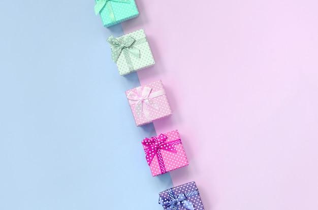 Kleine geschenkboxen in verschiedenen farben mit bändern liegen auf einem violetten und rosa