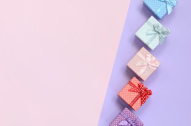 Kleine geschenkboxen in verschiedenen farben mit bändern liegen auf einem violetten und rosafarbenen farbhintergrund