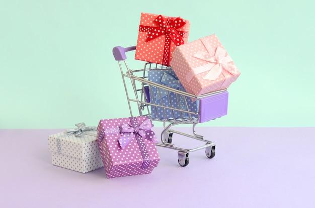 Kleine geschenkboxen in verschiedenen farben mit bändern liegen im einkaufswagen auf violettem und blauem pastellhintergrund