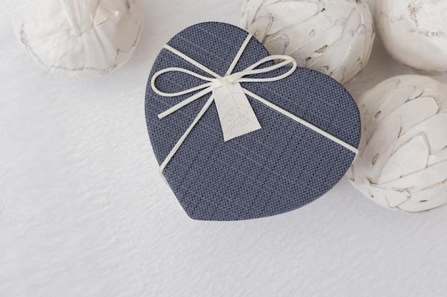 Kleine geschenkverpackung in form eines herzens. ein geschenk zum valentinstag. ansicht von oben. kopieren sie platz.