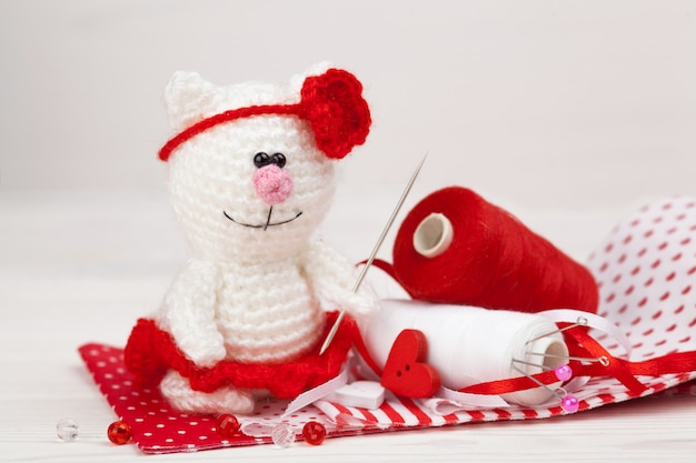 Kleine gestrickte weiße katze mit gegenständen für näharbeit. handgemacht, nahaufnahme. amigurumi