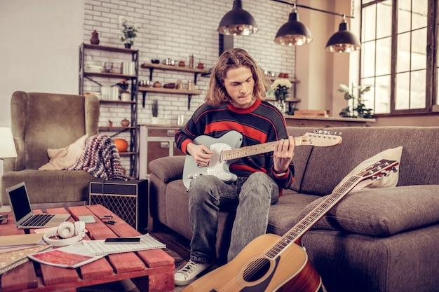 Kleine gitarre. blonder, talentierter, inspirierter student mit bob-schnitt, der seine neue kleine gitarre spielt