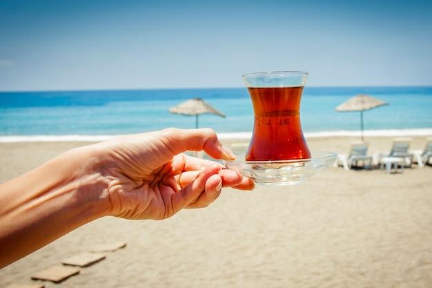 Kleine glasschale mit tee auf dem hintergrund des blauen meeres, des strandes und der sonnenschirme.