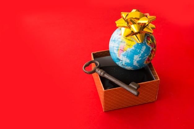 Kleine globale karte mit bogen nahe präsentkarton und schlüssel