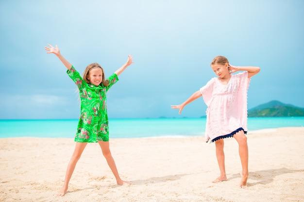 Kleine glückliche lustige mädchen haben viel spaß am tropischen strand, der zusammen, sonniger tag mit regen im meer spielt
